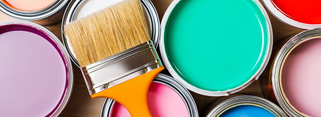 Pincel sobre diversos baldes de tinta abertos. As cores que aparecem são verde, lilás, entre outras.