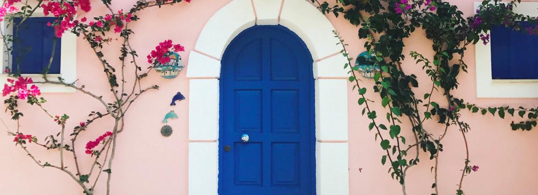 Fachada de casa com janelas e porta azul escuro, com bordas de cor branca e paredes rosa claro.