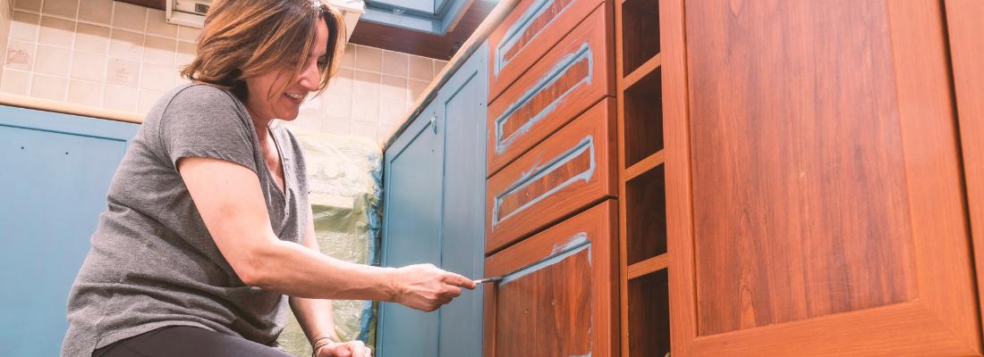 Mulher pintando balcão de madeira com esmalte sintético.