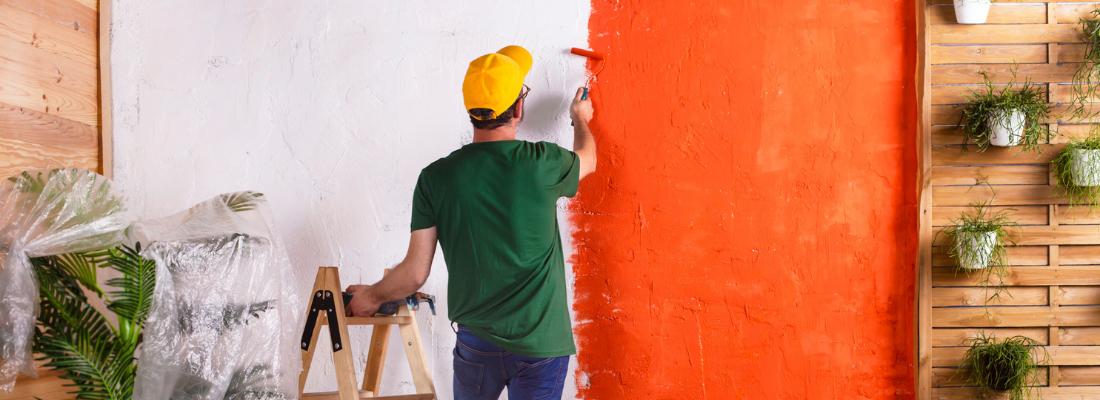 Homem pintando, com um rolo de pintar, uma parede da cor laranja.