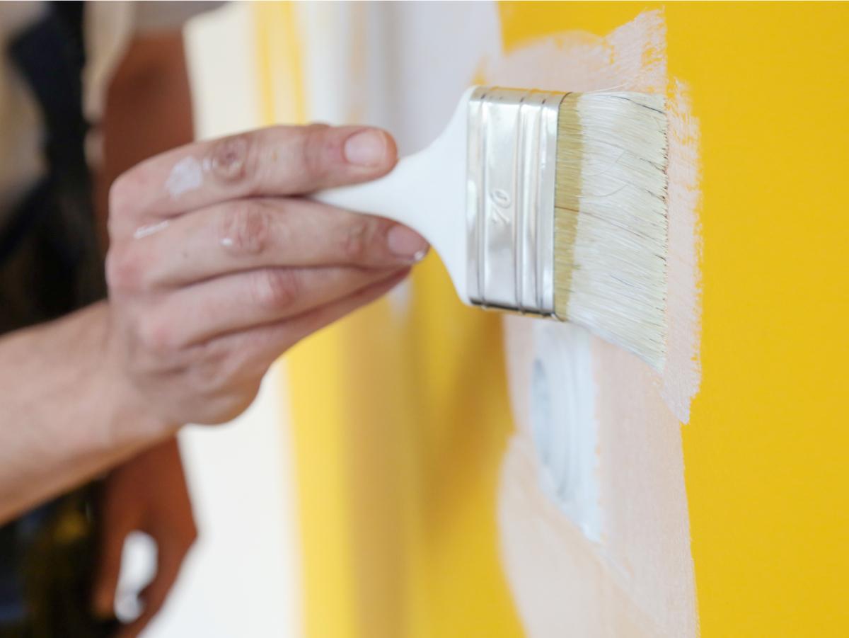 Parede amarela sendo pintada de branca. Apenas a mão do pintor, segurando o pincel, aparece na foto.